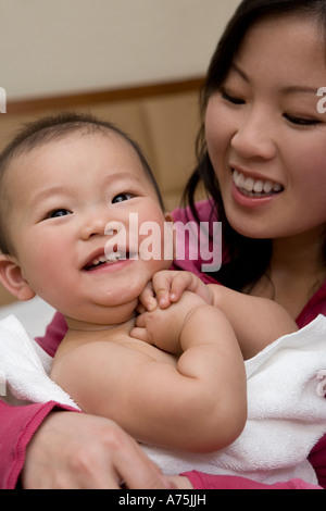 Woman wrapping her baby in a towel - Stock Photo