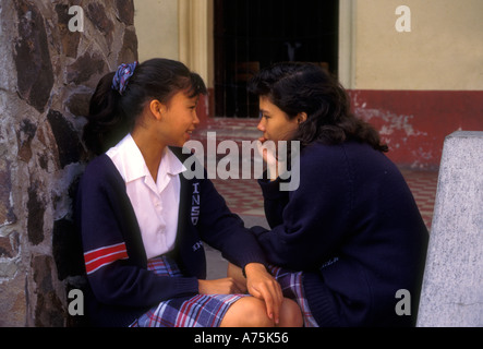 2 two Guatemalan girls female students schoolgirls friends talking at school in Antigua in Sacatepequez Department - Stock Photo