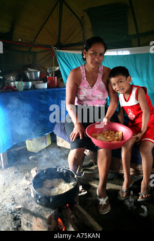 Family cooking inside a shelter on the outskirts of Trinidad, badly effected by flooding, Beni, Bolivia, South America - Stock Photo