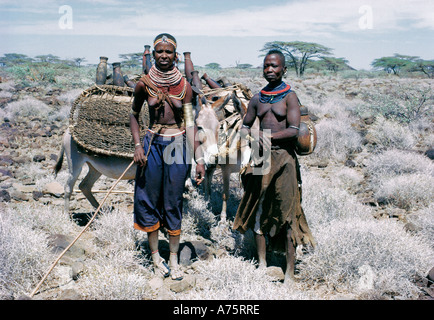 Two Turkana women with their donkeys and belongings during a migration Northern Kenya East Africa - Stock Photo