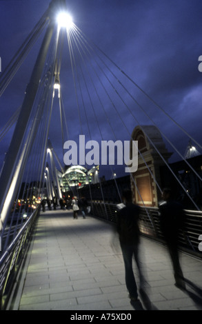 Pedestrians at night on new Hungerford bridge charing cross london England UK Eu Europe - Stock Photo