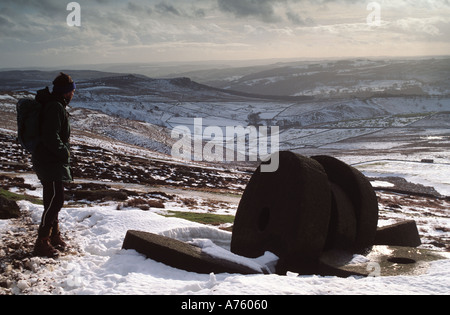 Winter Walker in the snow and Abandoned millstones  below 'Stanage Edge' in Derbyshire 'Great Britain' - Stock Photo