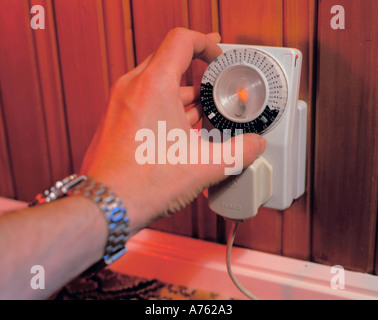 Domestic timer switch being set to operate a remote lamp, UK. - Stock Photo