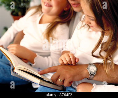 young children reading book with father - Stock Photo