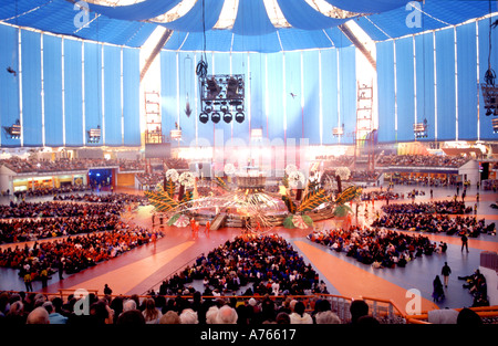 Large groups of people seated in the main events arena inside the millennium dome year 2000 exhibition North Greenwich - Stock Photo