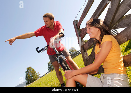 Couple having a rest, woman leaning on wooden railing - Stock Photo