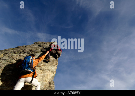 Young couple climbing on mountain peak, man helping woman, rear view