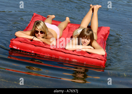 Two teenage girls (16-17) floating on air bed in lake, tilt view - Stock Photo