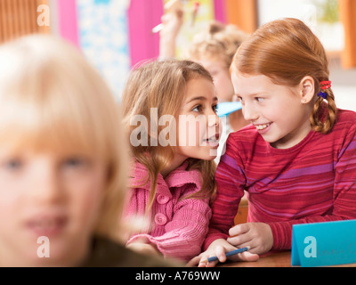 Girls (4-7) whispering in classroom - Stock Photo