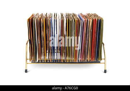 Side on view of old vinyl 45's records stacked in a kitsch seventies holder on a pure white background. - Stock Photo