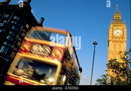 Tourist double decker bus driving past Big Ben and Portcullis House - slow shutter speed for motion blur of the - Stock Photo