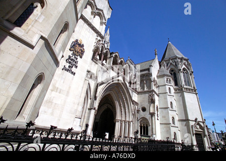 Wide angle view of the main entrance to the Royal Courts of Justice aka Law Courts against a blue sky. - Stock Photo
