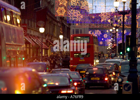 Compressed perspective rush hour traffic, Christmas lights and shoppers down Regent Street in the evening. - Stock Photo