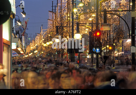 Compressed perspective rush hour traffic, Christmas lights and shoppers down Oxford Street in the evening. - Stock Photo