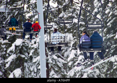 Close up compressed perspective of skiers and snowboarders on a chairlift at the Sierra Ski Resort, Lake Tahoe. - Stock Photo