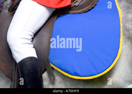 Close up of the saddle and numnah on a horse and traditionally dressed rider at the races. - Stock Photo