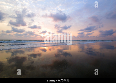 A colourful sunset and clouds reflected in the receeding water on the beach. - Stock Photo