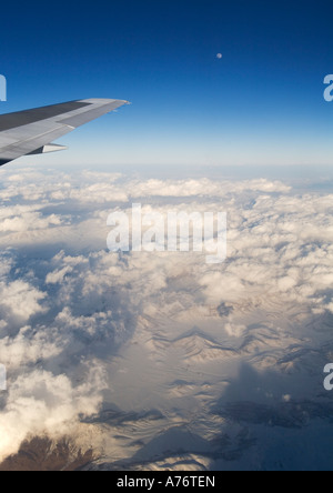 Aerial view of snow covered mountains at dusk flying over Turkey in winter with aircraft wing tip against blue sky - Stock Photo