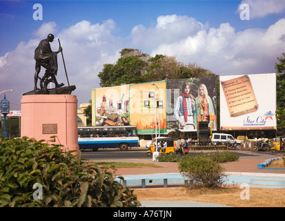 Statue of Gandhi looks down from monument as though watching the passing traffic on the promenade sea front road - Stock Photo