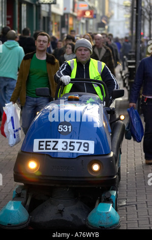 Motorised street pavement cleaner driven by local council worker in crowd out christmas shopping in Belfast Christmas - Stock Photo