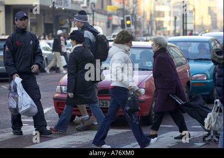 people out christmas shopping in Belfast cross pedestrian crossing in front of cars Christmas Eve Northern Ireland - Stock Photo