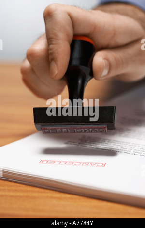 Man Using 'Cancelled' Stamp - Stock Photo