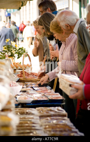 Shoppers buying fresh organic  local meat, eggs  and other food at Aberystwyth Farmers Market, Ceredigion Wales - Stock Photo