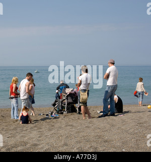 typical family group standing around waiting for something to happen on a  British beach on holiday at the seaside - Stock Photo