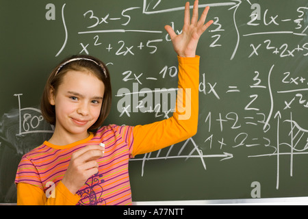11yo girl are standing with chalk in hand She s holding one arm triumphantly up Behind her there s greenboard with - Stock Photo