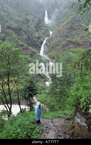 Waterfall and lonely traveler in foreground in Syange surroundings Annapurna area Nepal - Stock Photo