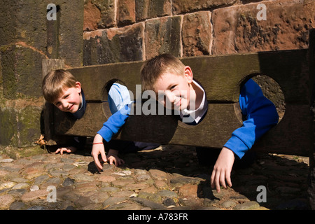 UK Cheshire Vale Royal Great Budworth two boys in village stocks at St Marys Parish church lych gate - Stock Photo