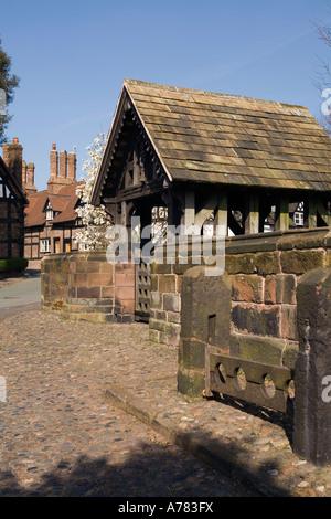 UK Cheshire Vale Royal Great Budworth village stocks at St Marys Parish church lych gate - Stock Photo