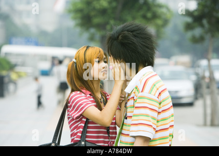 Teenage couple in urban setting, girl touching boy's face - Stock Photo