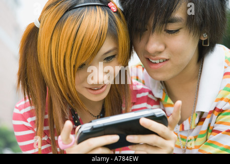 Teenage couple using portable video game - Stock Photo