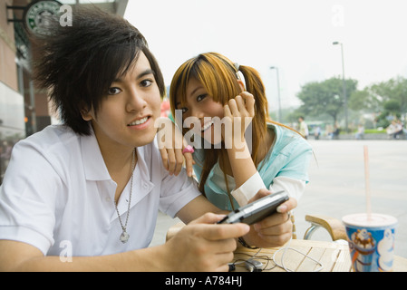 Teenage couple sitting at outdoor cafe, boy holding video game - Stock Photo