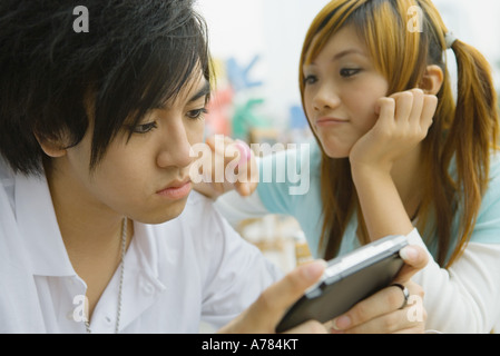 Teenage couple, boy playing video game while girl pesters him - Stock Photo