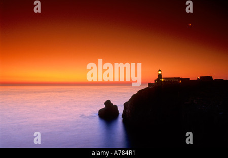 Sundown at the lighthouse of Cabo de Sao Vicente Sagres Costa Vicentina Algarve Portugal - Stock Photo