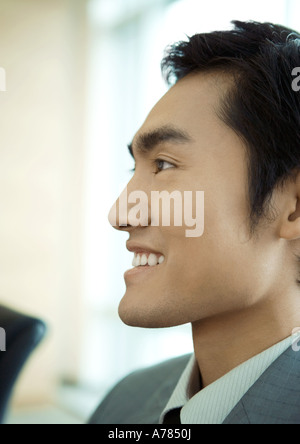 Businessman smiling, close-up side view of face - Stock Photo