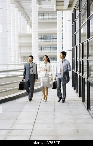 Three young executives walking side by side next to office building - Stock Photo
