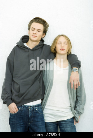 Young couple leaning against wall, man's arm around woman's shoulder, both closing eyes - Stock Photo