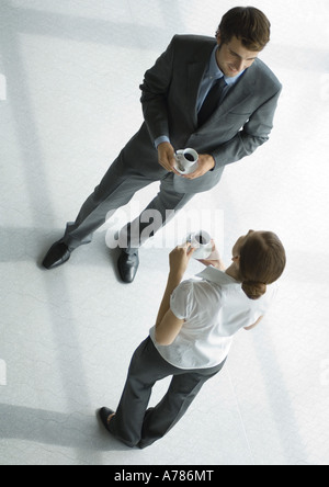 Office employees standing with coffee cups, full length, high angle view - Stock Photo
