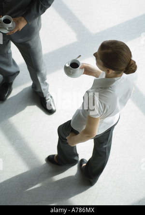 Office employees standing with coffee cups, high angle view - Stock Photo