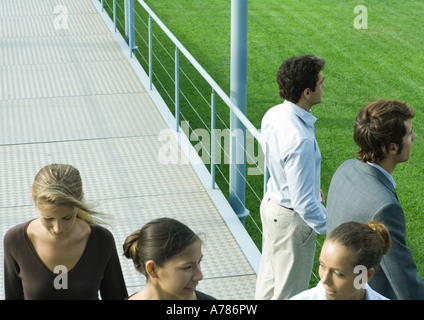 People standing and walking on walkway - Stock Photo