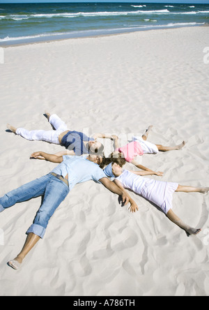 Family lying on sand, heads together and arms and legs out - Stock Photo
