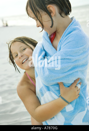 Two girls on beach, one wrapped in towel, the other holding girl around waist - Stock Photo