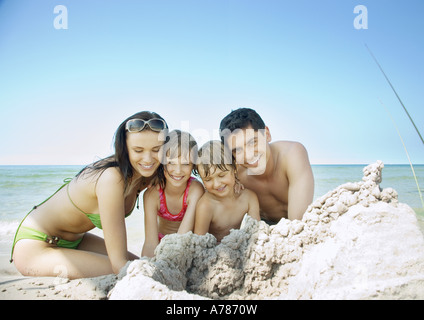 Family sitting on beach near pile of sand, portrait - Stock Photo