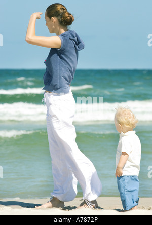 Young woman and toddler standing on beach - Stock Photo