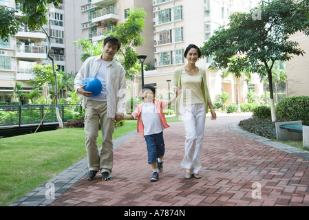 Mother and father walking with son, holding hands - Stock Photo