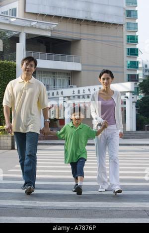Family crossing crosswalk, holding hands - Stock Photo