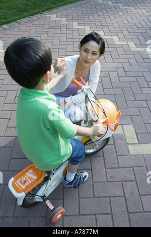 Boy on bike with training wheels and mother - Stock Photo